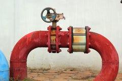 Conduites d'eau industrielles en métal rouillé rouge avec une valve image libre de droits