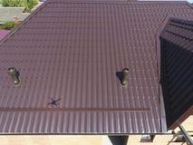 Conduits d'air sur le toit en métal Le toit de la feuille ondulée Toiture de forme onduleuse de profil en métal Image libre de droits