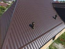 Conduits d'air sur le toit en métal Le toit de la feuille ondulée Toiture de forme onduleuse de profil en métal images libres de droits