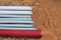 Conduits souterrains ridés par faisceau couverts de sable Images libres de droits