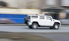 Condução de carro enorme branca do suv do hummer rapidamente, apressando-se para a frente Fotografia de Stock Royalty Free