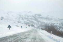 Condurre un'automobile sulla strada bianca e nevosa con un forte vento Scena e bufera di neve del tempo di inverno Tempesta di in fotografia stock