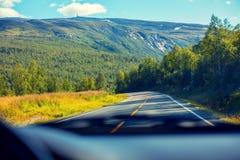 Condurre un'automobile sulla strada della montagna Immagine Stock