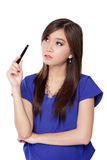Condused young Asian businesswoman. Young Asian woman holding a pen while looking up thinking for idea with confused face, isolated on white background Royalty Free Stock Image