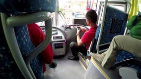 Condutor do ônibus que usa o telefone celular no ônibus do passageiro vídeos de arquivo