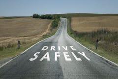 Conduza com segurança a mensagem na estrada asfaltada Imagens de Stock Royalty Free