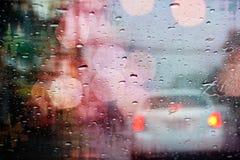 Conduzindo na chuva, pingos de chuva na janela de carro com bokeh claro Fotografia de Stock Royalty Free