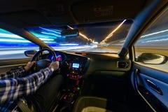 Conduzindo no cenário da noite, mãos no volante, tempo da chuva da noite foto de stock royalty free