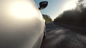 Conduzindo o carro ao longo da estrada com muitas árvores video estoque