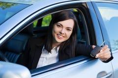 Conduzindo o conceito - mulher de sorriso feliz com chave do carro Fotografia de Stock