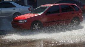 Conduzir carros em uma estrada inundada durante as inundações causadas pela chuva ataca Flutuador dos carros na água, inundando r imagem de stock