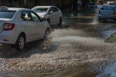 Conduzir carros em uma estrada inundada durante as inundações causadas pela chuva ataca Flutuador dos carros na água, inundando r imagens de stock royalty free