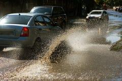 Conduzir carros em uma estrada inundada durante as inundações causadas pela chuva ataca Flutuador dos carros na água, inundando r imagens de stock