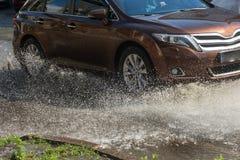 Conduzir carros em uma estrada inundada durante as inundações causadas pela chuva ataca Flutuador dos carros na água, inundando r fotografia de stock royalty free