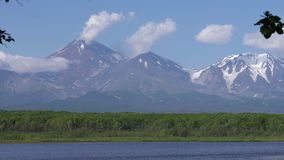 Cone of active volcano, mount lake, green summer forest, clouds drifting across blue sky near mountains. Zoom in view
