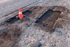 Cone alaranjado branco do perigo do tráfego no reparo da estrada asfaltada fotografia de stock royalty free