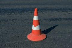 Cone arrastado do tráfego na estrada escura do betume fotografia de stock