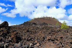 Ash Volcano and Lava Bed in Newberry National Monument, Oregon. The cone of an ash volcano is towering above the wide open beds of block lava that make up the Royalty Free Stock Images