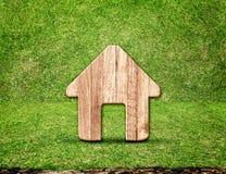Ícone de madeira home na sala da grama verde, conceito de Eco Fotografia de Stock Royalty Free