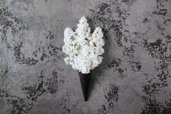 Cone do waffle com o ramalhete lilás da flor no fundo cinzento foto de stock royalty free