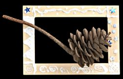 Cone in frame. Cedar cone in wooden frame painted by a child Stock Photos