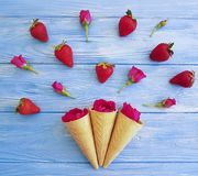Cone for ice cream, strawberry, fresh pattern creative rose flower pattern on a blue wooden. Cone for ice cream, strawberry, rose flower pattern on a blue wooden Royalty Free Stock Photography