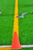 Cone & lacrosse stick on a turf field. An orange cone marke the corner of the out of bound lines on a turf field with a lacrosse stick in the background Royalty Free Stock Photos