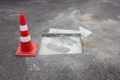 Cone laid on the damaged road waiting for repair. Notifications on the road Stock Image
