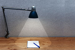 The cone of light from a table lamp. On a table falls and notebook Royalty Free Stock Photos