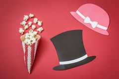Cone and popcorn with paper prop hats on red background, cinema creative concept. Flat lay of cone and popcorn with man and woman paper prop hats on red Royalty Free Stock Photos