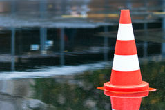 Cone in a puddle V2. Warning cone in a puddle at the street Stock Image