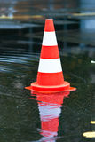 Cone in a puddle V3. Warning cone in a puddle at the street Royalty Free Stock Photo