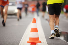 Cone on road between running people. Big color cone on road between running people, close-up view Royalty Free Stock Image