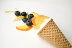 Cone. Scoop of white ice cream. Blueberries. Cone. Scoop of white ice cream. Ice cream cone with fruits and berries. Summer stock photo