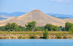 Cone Shaped Mountain on the Colorado prairie. Cone shaped Haystack Mountain near Boulder on the Colorado prairie by a small lake royalty free stock photography