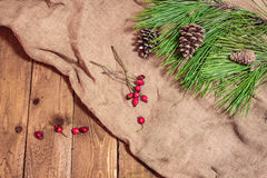 Cone and spruce branch on old cloth with red berrys. New year and christmas decoration on wooden table Royalty Free Stock Photography