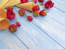 Cone wafflefor ice cream, strawberry, dessert refreshment pattern creative rose flower pattern on a blue wooden. Cone waffle ice cream, strawberry, rose flower stock photography
