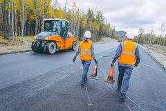 Cone worker asphalting. Construction roller pavement repair Royalty Free Stock Photo