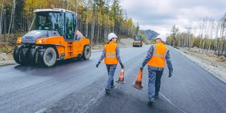 Cone worker asphalting. Construction roller pavement repair Stock Photos