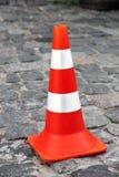 The cone zone, orange road cone. The cone zone, orange road cone with white stripes on the road from paving stones Royalty Free Stock Photo