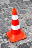The cone zone, orange road cone. The top view on cone zone, orange road cone with white stripes on the road from paving stones Royalty Free Stock Photography