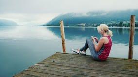 Conectado sempre Uma mulher usa um smartphone, senta-se em um lugar pitoresco perto de um lago da montanha nos cumes video estoque