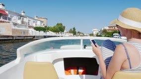Conectado siempre: mujer con un teléfono en su mano en los flotadores de un barco en el canal La ciudad de vacaciones de Empuriab almacen de metraje de vídeo