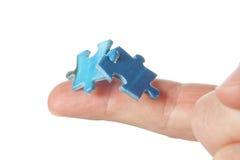Conectando dois enigmas em seu dedo. Fotos de Stock Royalty Free