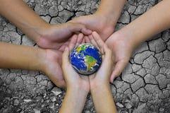 Conecte a tierra el planeta en la mano asiática de los niños aislada en el barr árido de tierra Foto de archivo libre de regalías