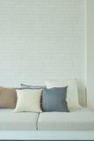 Conecte a tierra las almohadas del color de tono en el sofá con la pared de ladrillo blanca Fotos de archivo