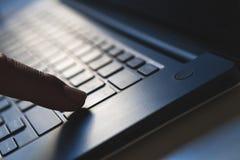 Conectividad y acceso a datos, finger que pulsa la tecla de entrada en el ordenador portátil Foto de archivo libre de regalías