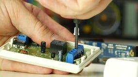 Conectores da fixação do trabalho do técnico em uma placa eletrônica que usa uma chave de fenda filme