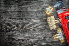 Conectores da tubulação da chave de macaco do encanamento na placa de madeira do vintage imagens de stock royalty free