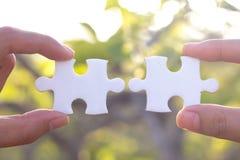 Conectores de duas mãos da parte do enigma de serra de vaivém, backgro verde natural imagem de stock royalty free